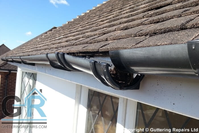 A roof in need of guttering repairs and minor roof repairs on a detached property in London.