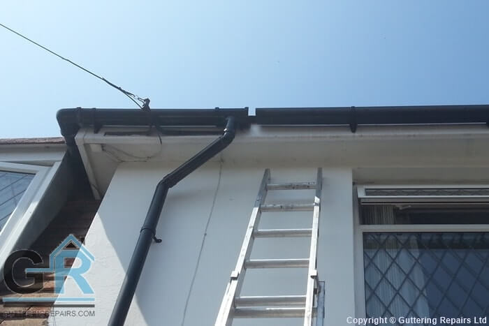 Guttering Repairs Ltd undertaking a rain gutter repair on a residential property.
