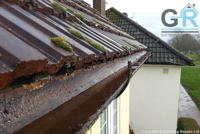 Residential cast iron roof gutter cleared of leaves and debris in East Sussex.