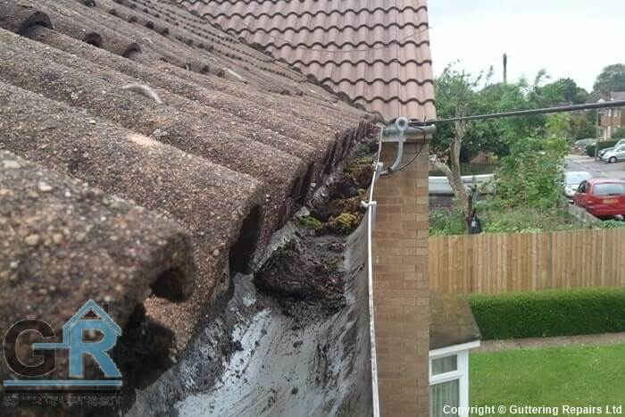 Roof gutter repair and cleaning on a terraced house roof.