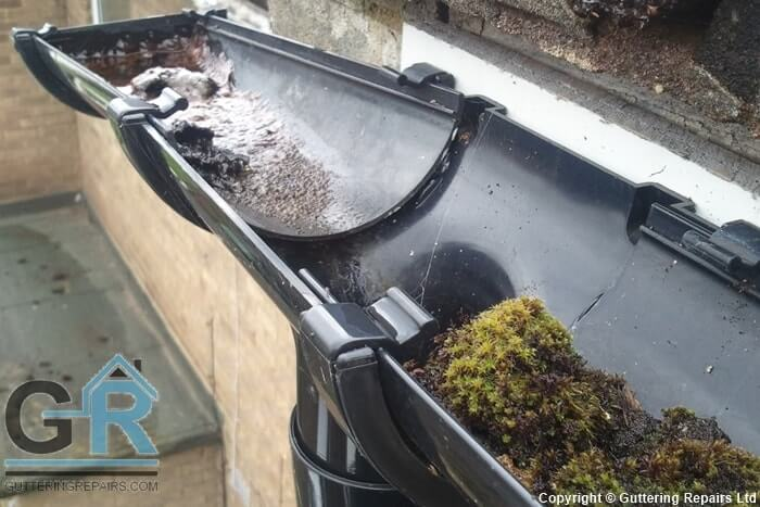 Roof gutter repairs and cleaning on a block of residential flats.