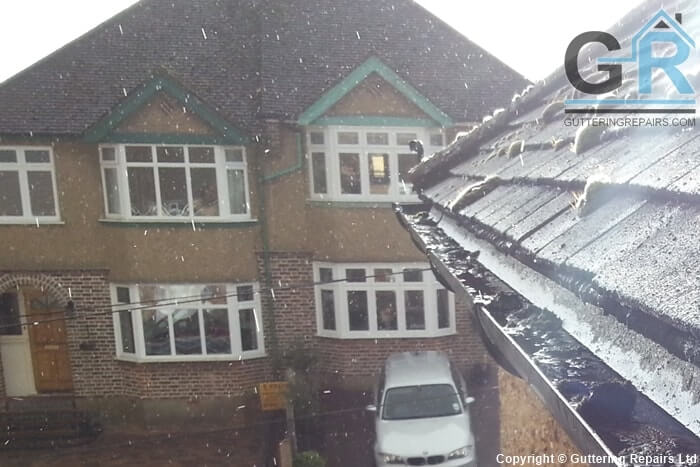 Roof gutter cleaning and repairs on a semi detached house roof.