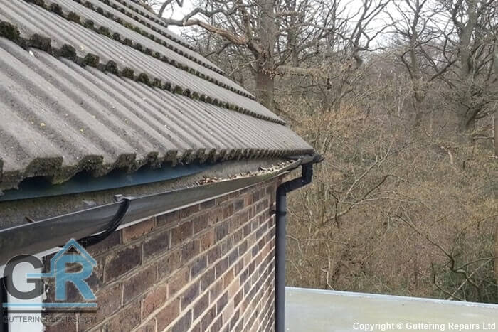 Sagging PVC roof gutter causing rainwater to overflow on a residential property.